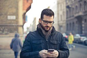 Homem usando óculos e mexendo no celular